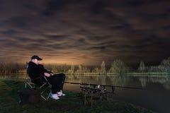 渔夫在繁星之夜看在标尺的,耐心 库存照片