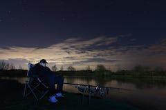 渔夫在繁星之夜,在看的椅子坐标尺,耐心 免版税库存照片