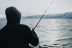 渔夫在钓鱼竿的抓住鱼在冬天 库存照片