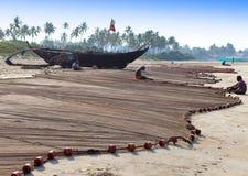 渔夫在2014年2月01日的早晨渔以后修理鱼网在果阿,印度 库存图片