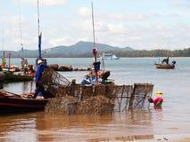 渔夫在他的小船的carrys网 库存照片