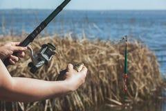 渔夫在他的被捉住的手上举行钓鱼和有卷轴的一把标尺以河为背景 免版税库存图片