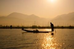 渔夫在Inle湖抓食物的鱼在日出 免版税库存照片