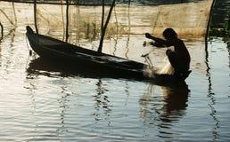 渔夫坐划艇,拾起网 库存照片