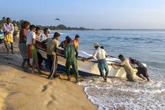 渔夫扯拽在海滩上的一条小船 免版税库存照片