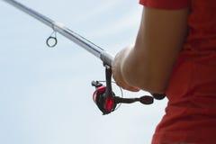 渔夫抓一条鱼 一位渔夫的手有一个实心挑料铁杆手中特写镜头的 旋转渔卷轴 库存照片