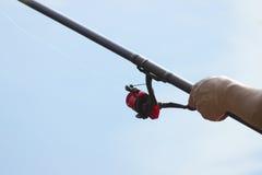 渔夫抓一条鱼 一位渔夫的手有一个实心挑料铁杆手中特写镜头的 旋转渔卷轴 免版税库存图片