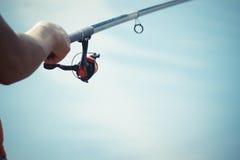 渔夫抓一条鱼 一位渔夫的手有一个实心挑料铁杆手中特写镜头的 旋转渔卷轴 免版税库存照片