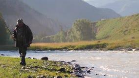 渔夫抓住钓鱼反对山风景的背景 渔夫旅游吼声在山河 业余爱好 影视素材