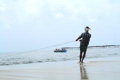 渔夫拉扯他的渔船 免版税图库摄影