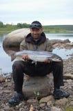 渔夫拿着在北河的河岸的一条大三文鱼 库存照片