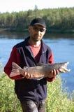 渔夫捉住了一条好的公三文鱼 免版税库存照片