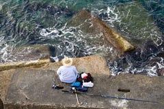 渔夫捕鱼展望期海运石头顶层 库存图片
