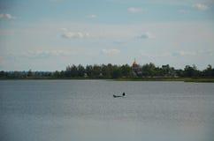 渔夫是在河的划船 免版税库存图片