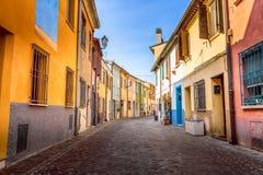 渔夫有五颜六色的房子和自行车的圣Guiliano村庄的狭窄的街道在清早在里米尼,意大利 免版税库存照片