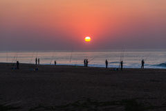 渔夫标尺海滩海浪日出 免版税库存照片
