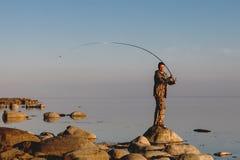 渔夫检查线,准备并且投掷诱饵入平安的水 库存图片