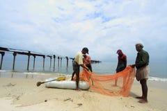 渔夫清洗鱼网在海滨 免版税库存照片
