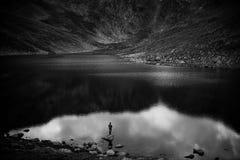 渔夫渔在山湖 免版税图库摄影