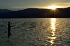 渔夫渔在McDonald湖在日落的冰川国家公园 免版税库存图片