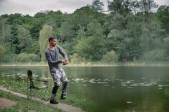 渔夫熔铸了在湖或河水的钓鱼竿 有转动的滑车的人在绿色森林健康生活方式 免版税库存图片