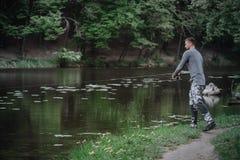 渔夫熔铸了在湖或河水的钓鱼竿 有转动的滑车的人在绿色森林健康生活方式 免版税图库摄影