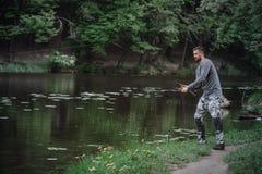 渔夫熔铸了在湖或河水的钓鱼竿 有转动的滑车的人在绿色森林健康生活方式 免版税库存照片