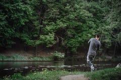 渔夫熔铸了在湖或河水的钓鱼竿 有转动的滑车的人在绿色森林健康生活方式 库存图片