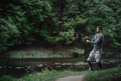 渔夫熔铸了在湖或河水的钓鱼竿 有转动的滑车的人在绿色森林健康生活方式 图库摄影