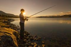 渔夫的剪影湖背景的  免版税库存图片