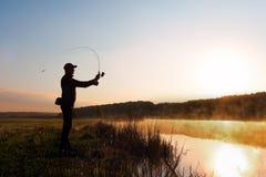渔夫的剪影黎明传染性的鱼的在河 冷的夏天早晨和薄雾在河 库存照片