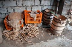 渔夫的存贮:老木桶,网,绳索 免版税库存照片