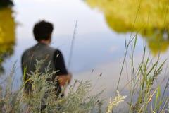 渔夫被弄脏的剪影河的在一个清楚的夏天d 库存图片