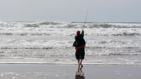 渔夫铸件到海浪里 库存图片
