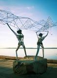 渔夫雕塑江边的 在海投掷网 库存照片