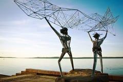 渔夫雕塑江边的 在海投掷网 库存图片
