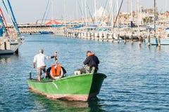 渔夫,有一条绿色小船的,在海滩在亚实基伦,以色列 库存图片