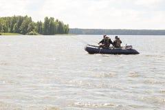 渔夫从小船的抓住鱼 免版税库存照片
