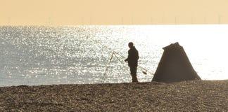 渔夫从海滩的海洋捕鱼 免版税图库摄影