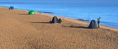 渔夫从海滩的海洋捕鱼 免版税库存图片