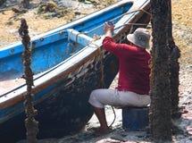 渔夫绘画渔船 免版税库存照片