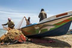渔夫从他们的网的排序鱼在Negombo的海滩在斯里兰卡 图库摄影