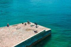渔夫从码头钓鱼 免版税库存图片
