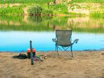 渔夫` s椅子和捕鱼设备在沙子河海岸夏令时,平静的爱好为夏天在假期放松 免版税库存图片