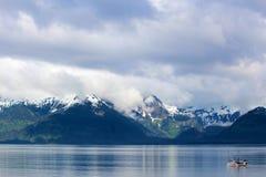 渔拖网渔船、山脉和天空 免版税库存图片