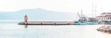 渔拖网渔船和一条小船在一个小镇Postira -克罗地亚,海岛胸罩的美丽的港口 库存照片