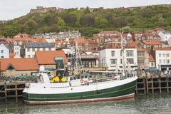 渔拖网渔船在小镇港口 库存图片
