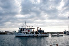 渔船到达口岸交付鲜鱼 免版税库存图片