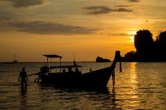 渔船和人剪影日落的在海海滩胜地在泰国、Krabi、Railey和Tonsai 免版税库存照片