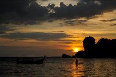 渔船和人剪影日落的在海海滩胜地在泰国、Krabi、Railey和Tonsai 图库摄影